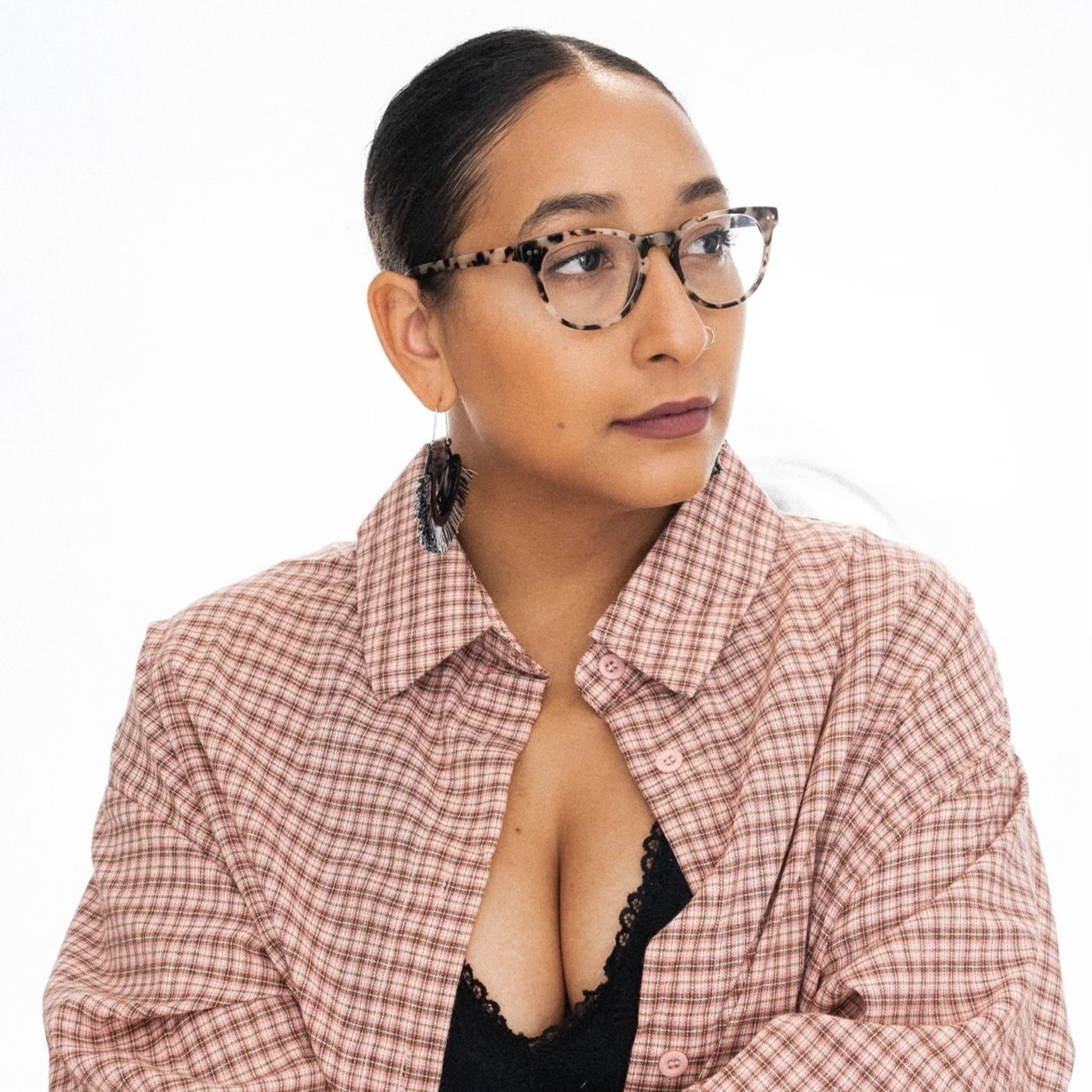 Danielle P. Williams wears tortoise shell glasses and an open button-down. She looks to her left.