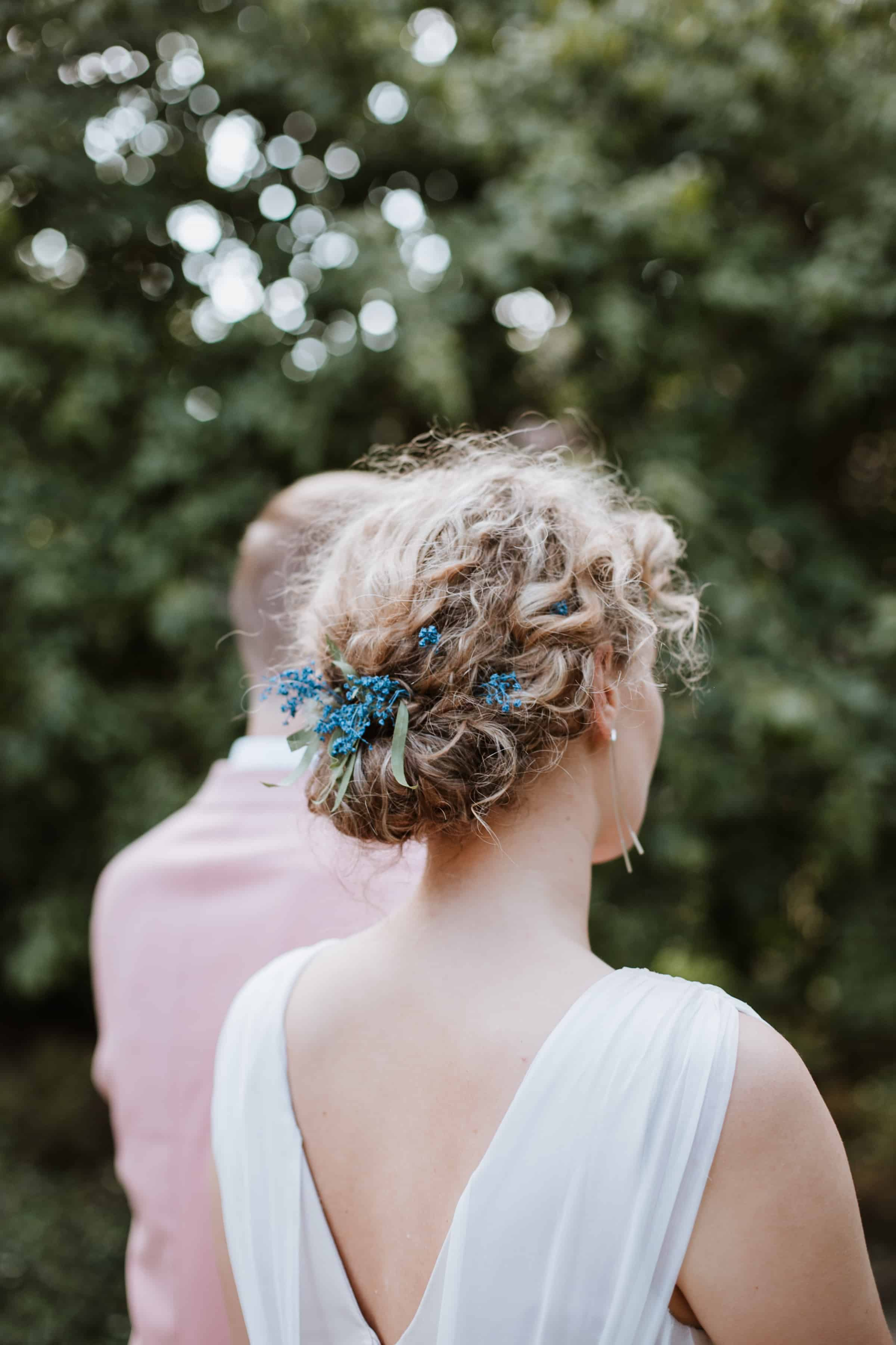 curly bride wears beautiful updo with natural blue flowers