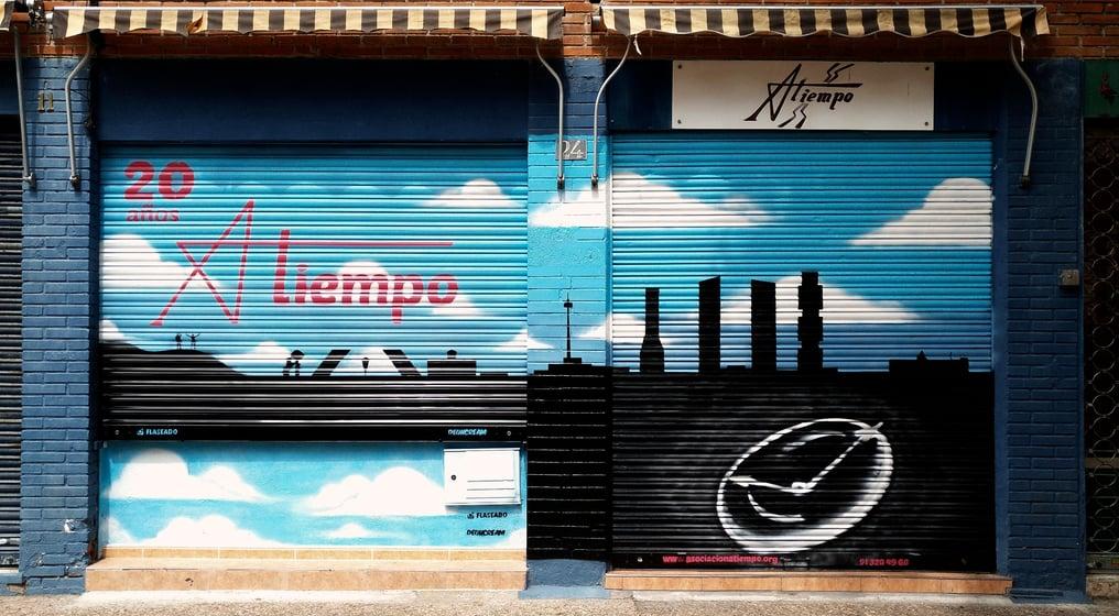 Graffiti cierre local asociación atiempo con skyline de Madrid