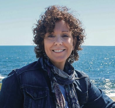 Aggie, with short curly hair and a denim jacket, stands in front of a bright blue sea.
