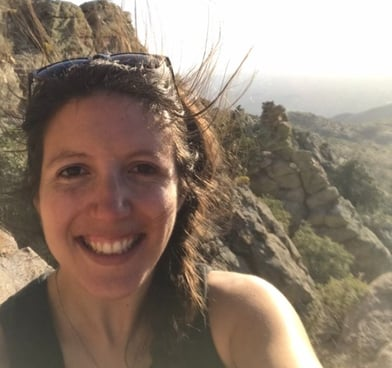 Image description: Sarah Ruth Bates smiles in front of a rocky desert landscape.