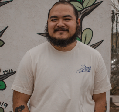 Antonio Villaseñor-Baca smiles at the camera, wearing a white T-shirt and standing against a mural.