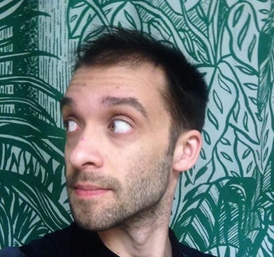Evan Fleischer looks to the side, standing in front of green patterned wallpaper.