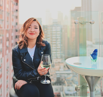 Jemimah Wei holds a glass of white wine and sits, smiling, on a rooftop overlooking a cityscape.