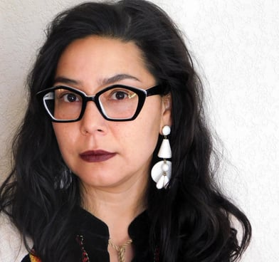 Felicia Rose Chavez looks at the camera wearing thick, angular glasses, large white earrings.