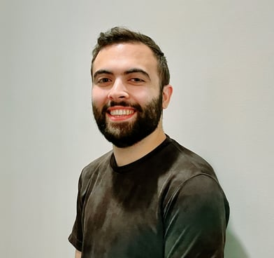 Tarik Dobbs smiles, standing in front of a white wall and wearing a black T-shirt.
