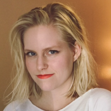Ellie Black smiles at the camera, wearing a white shirt and standing in front of an orange wall.