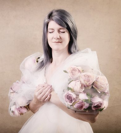 Photograph of a beautiful woman wearing a flower cape