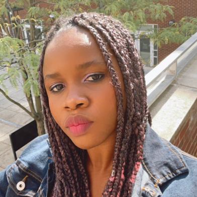 Adachioma Ezeano looks directly at the camera, her hair in braids, she wears a denim jacket.
