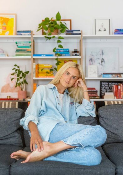 Natalie Warther sits on a grey couch in front of books and plants. She is blonde and wears denim.