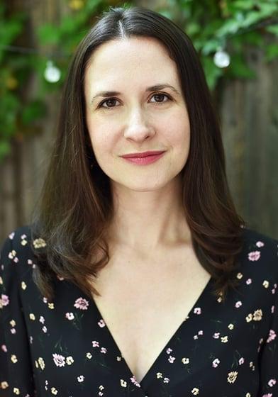 Katie Schorr has shoulder-length dark brown hair and brown eyes. She wears a black floral blouse.