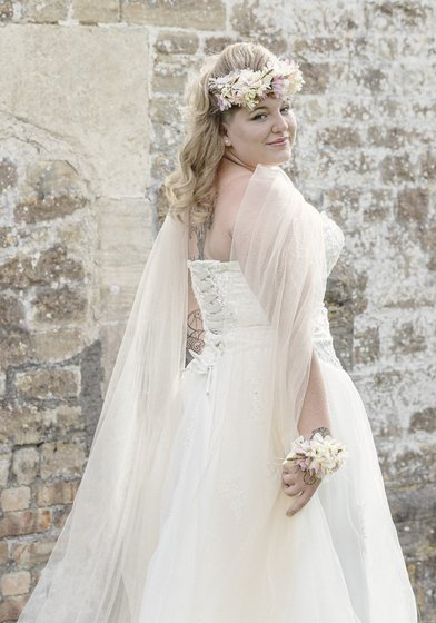 Image of a bride in front of a stone wall