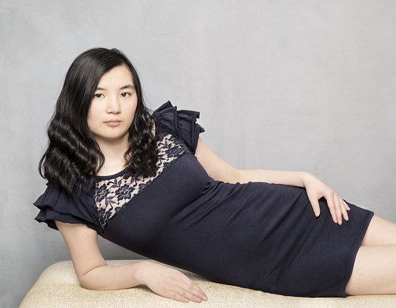 Photograph of a beautiful young woman reclining on a bench
