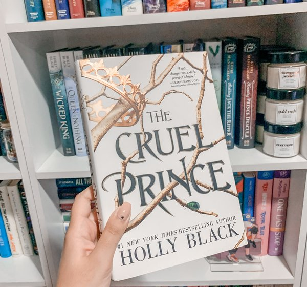 Mariah is holding up a hardcover copy of The Cruel Prince by Holly Black in front of her shelves.