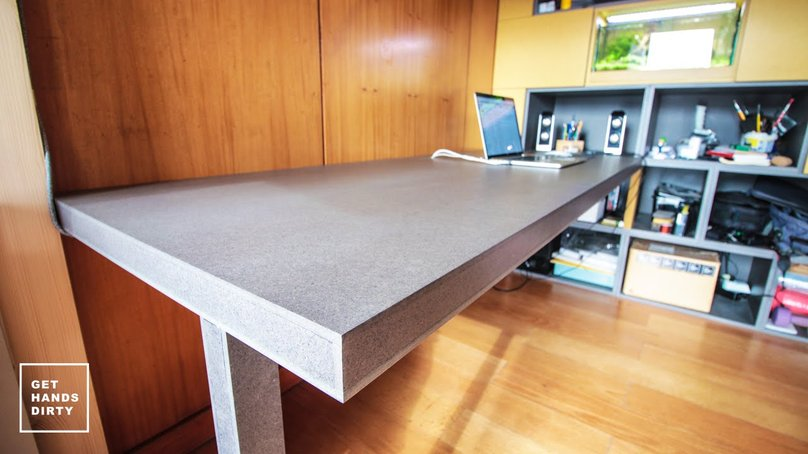An almost floating working desk underneath a loft bed built with colored MDF.