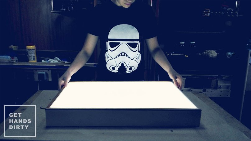 Woman standing in front of the custom-made LED light box.