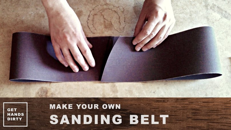 Hands around a piece of sandpaper roll in the shape of a sanding belt