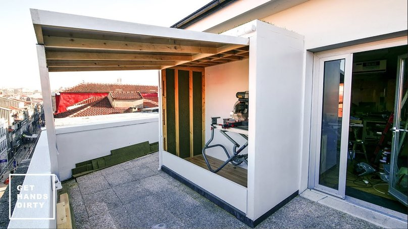 An outdoor shed in a small balcony. Grass over the roof.