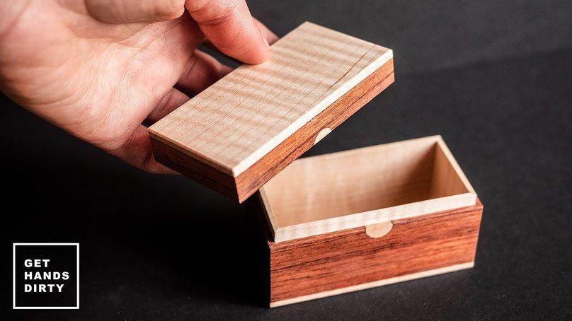 A hand holding a very small wooden box made out of maple, bubinga and leather.