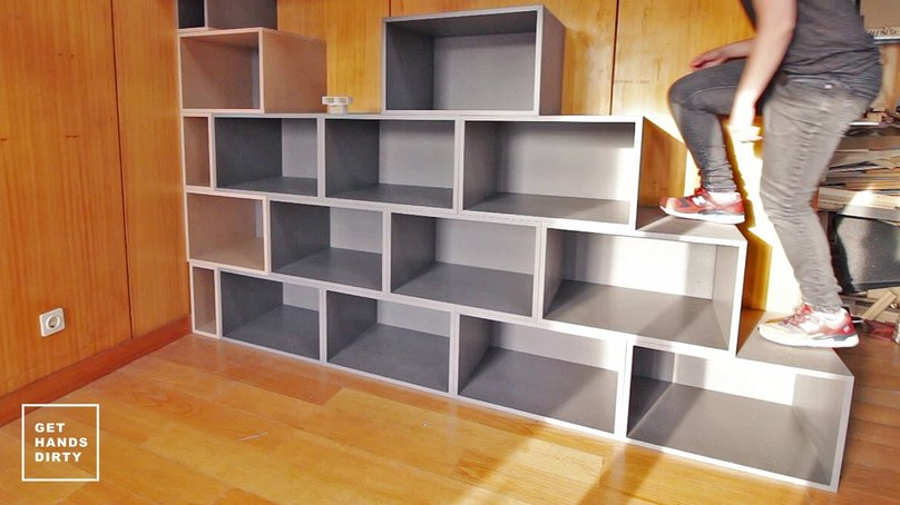 A person going up a staircase that is simultaneously a shelf.