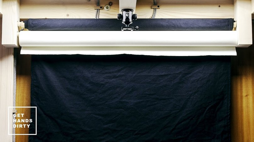 A rack with a black background roll and a white roll.