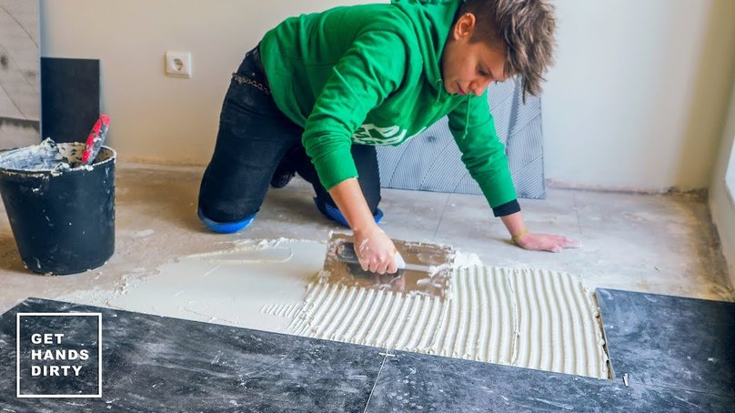 Applying cement to the floor in order to install the black ceramic tiles